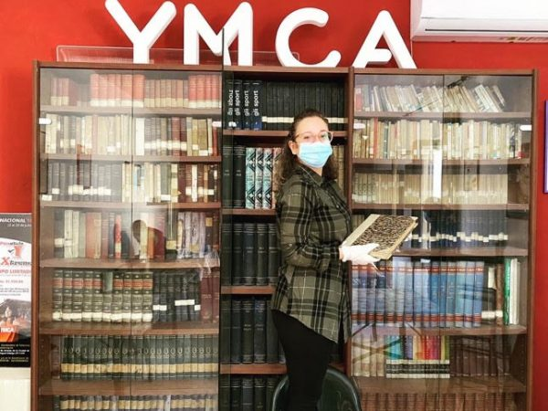 Francesca Natalone, wearing a mask and gloves, in front of a book shelve